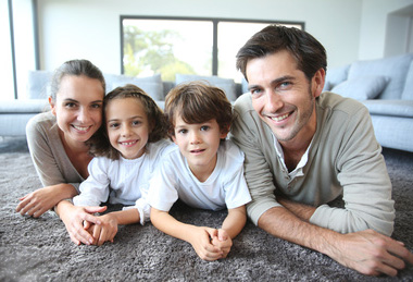 Junge Familie mit gesunder Haut liegt auf dem Teppich am Boden